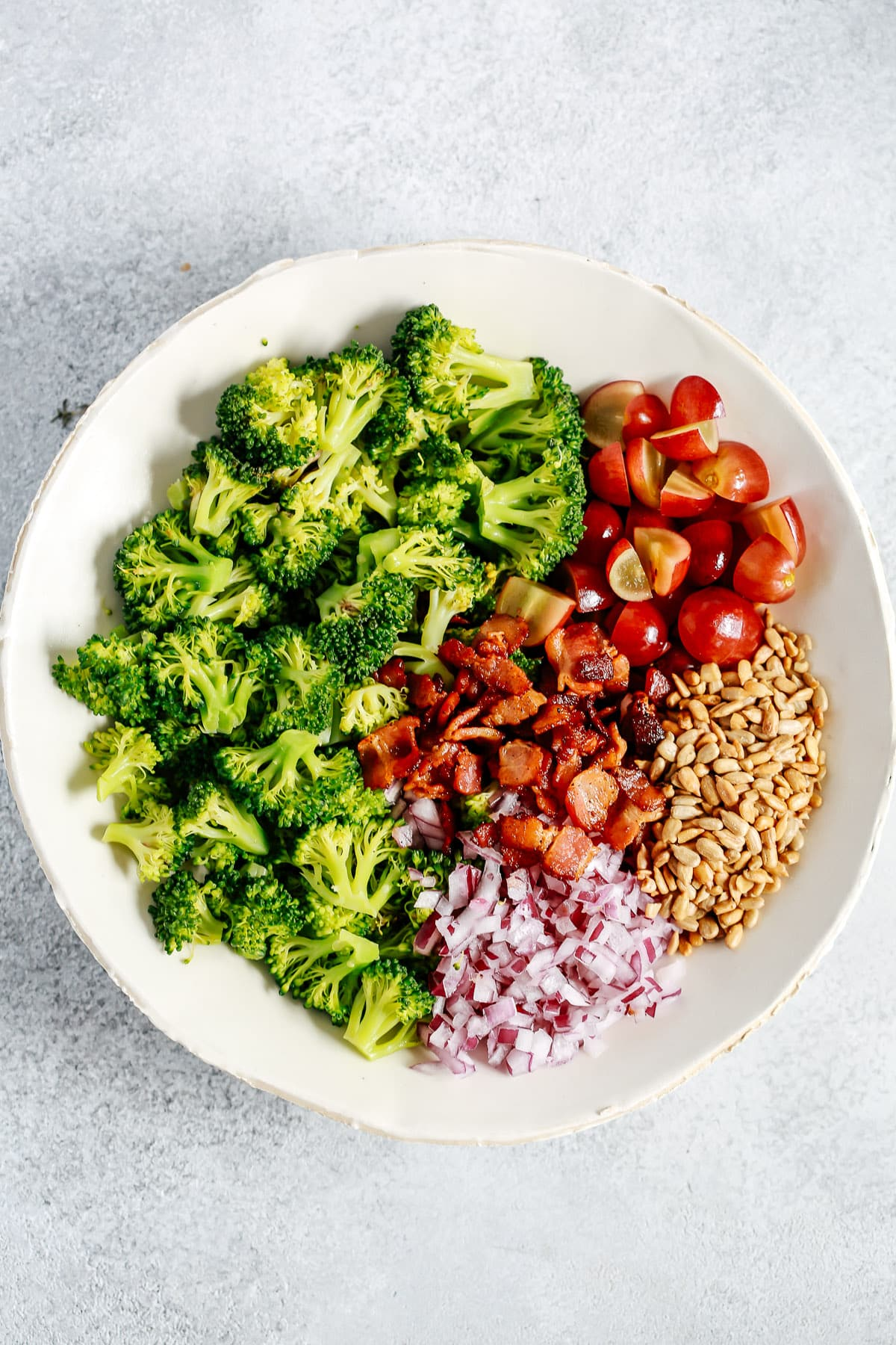 broccoli salad in bowl with ingredients separated into clusters