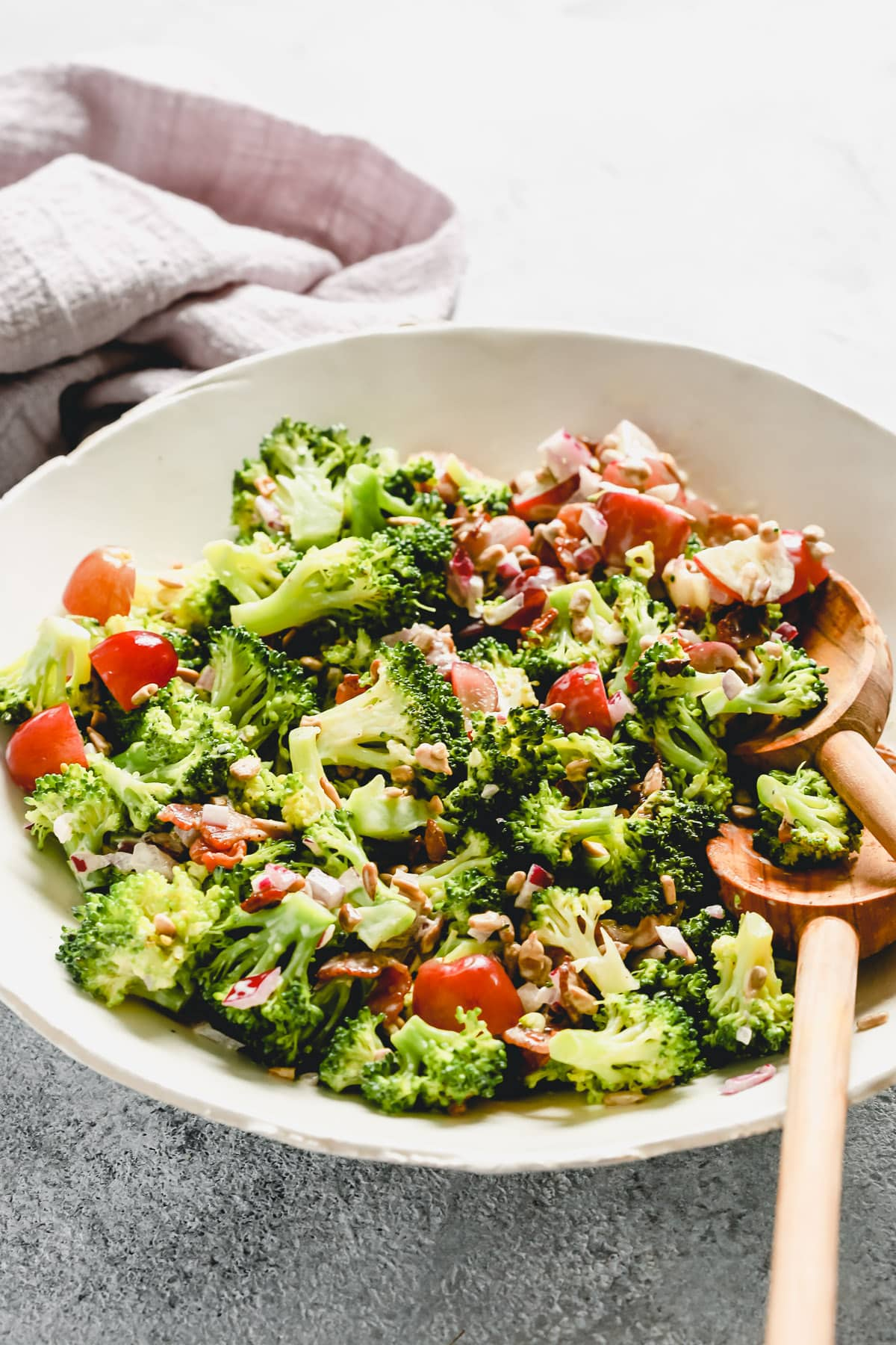 A white plate containing broccoli salad with two wooden spoons.