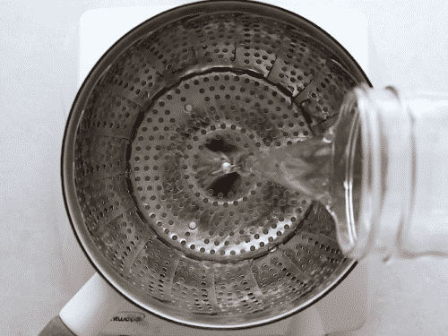 overhead view of someone filling a pan with water