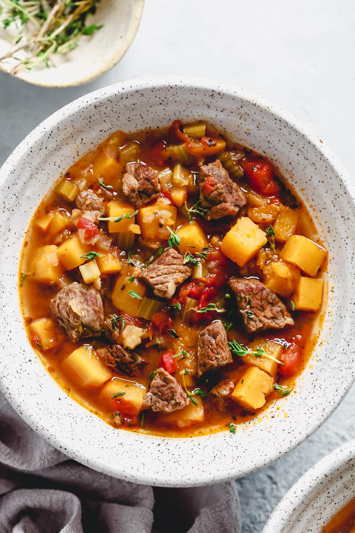 bowl of soup with beef, carrots, potatoes, and tomatoes