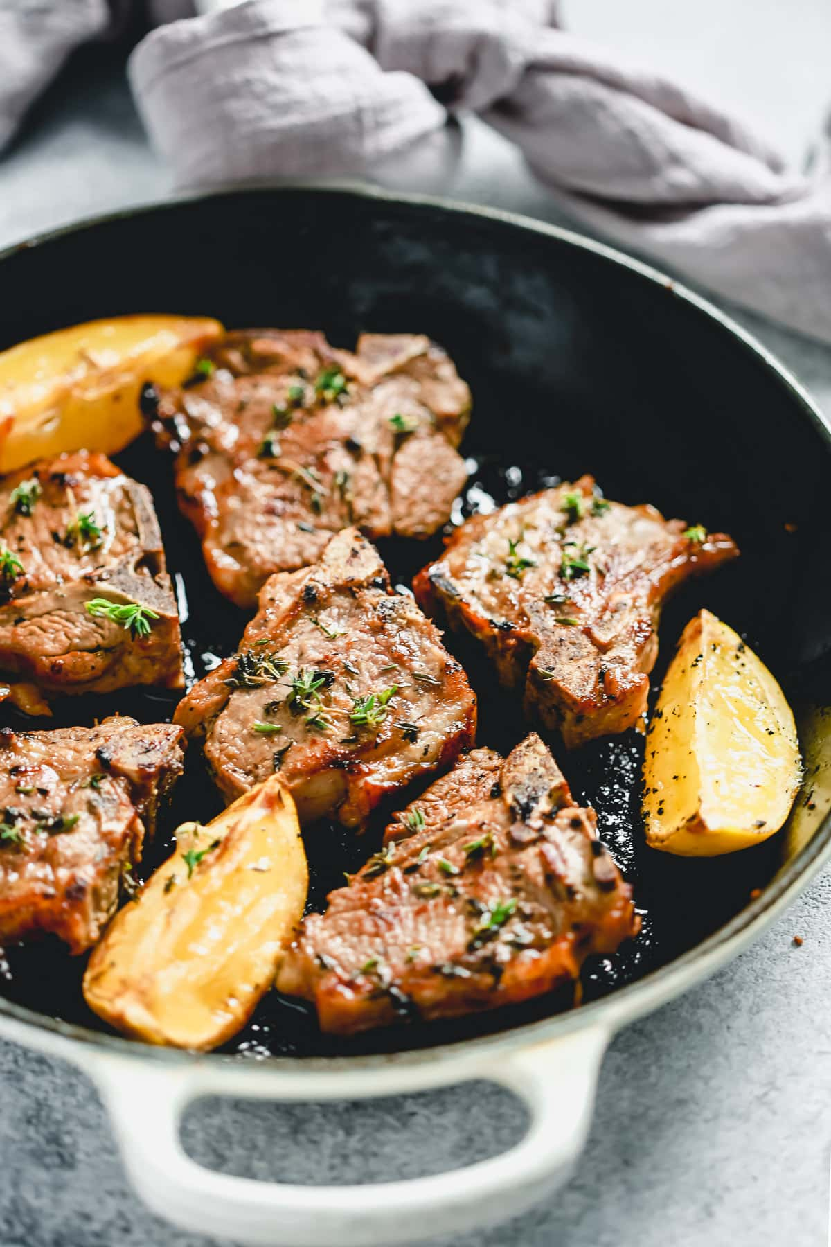 lamb chops cooking in pan with fresh lemon wedges and sprigs of thyme