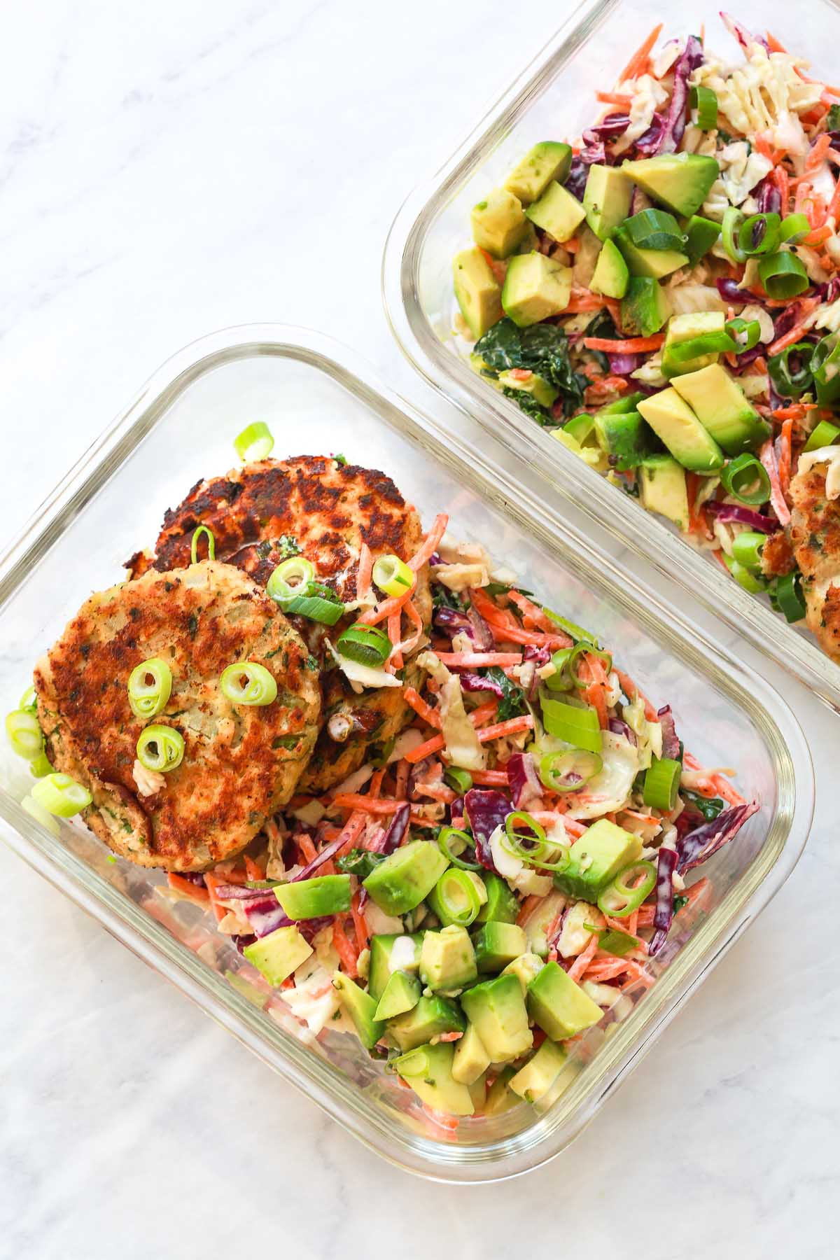 Two meal prep containers of salmon patties with coleslaw.