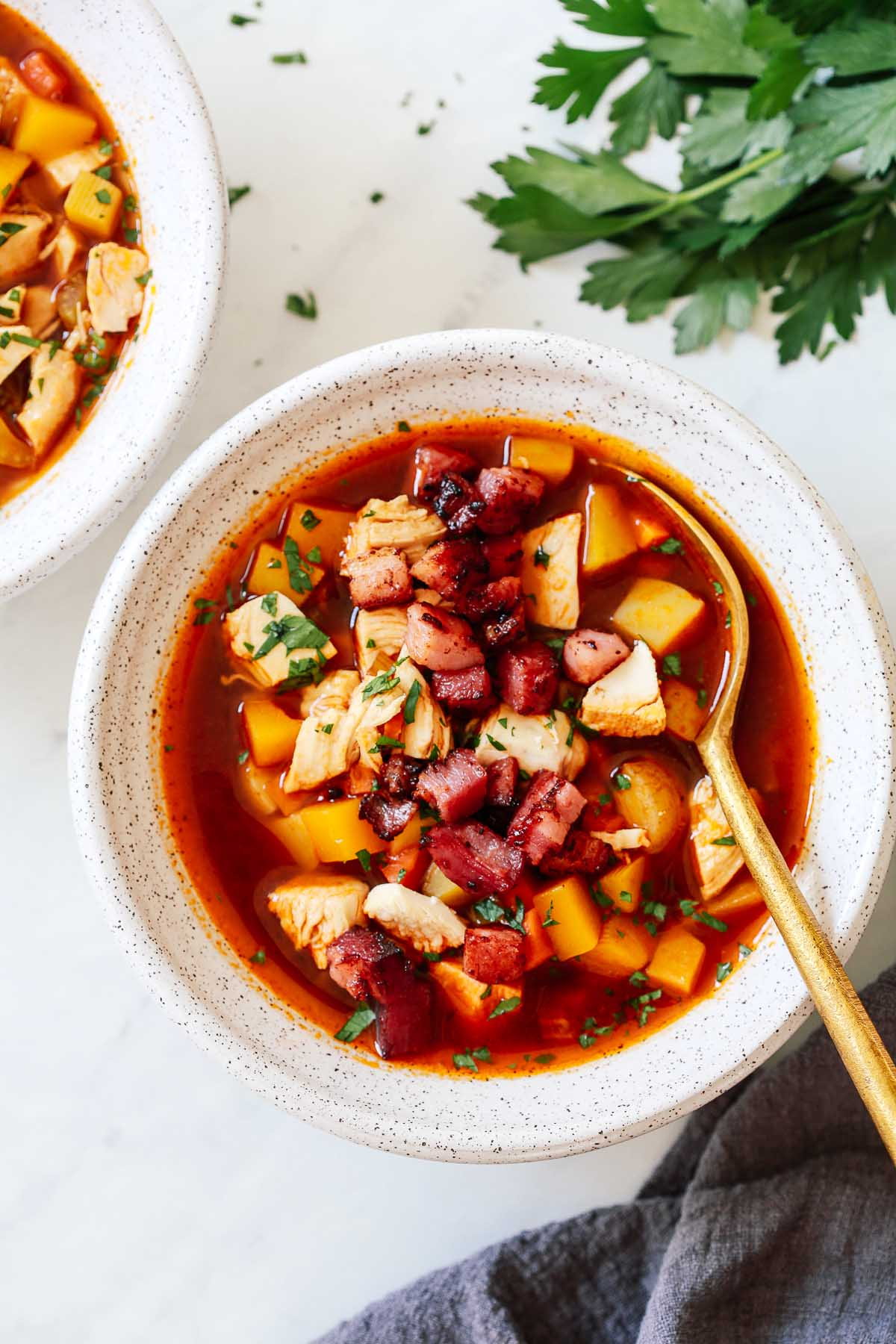 Turkey vegetable soup in a white bowl with a golden spoon inside.