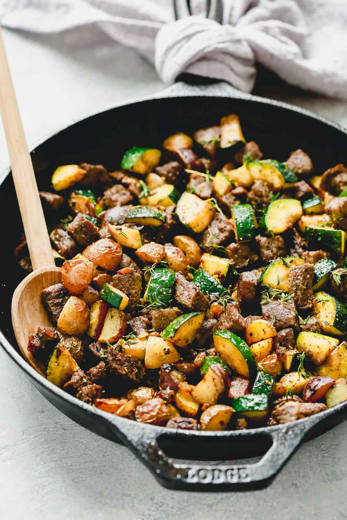 Beef and zucchini in a black cast iron with a spoon inside.