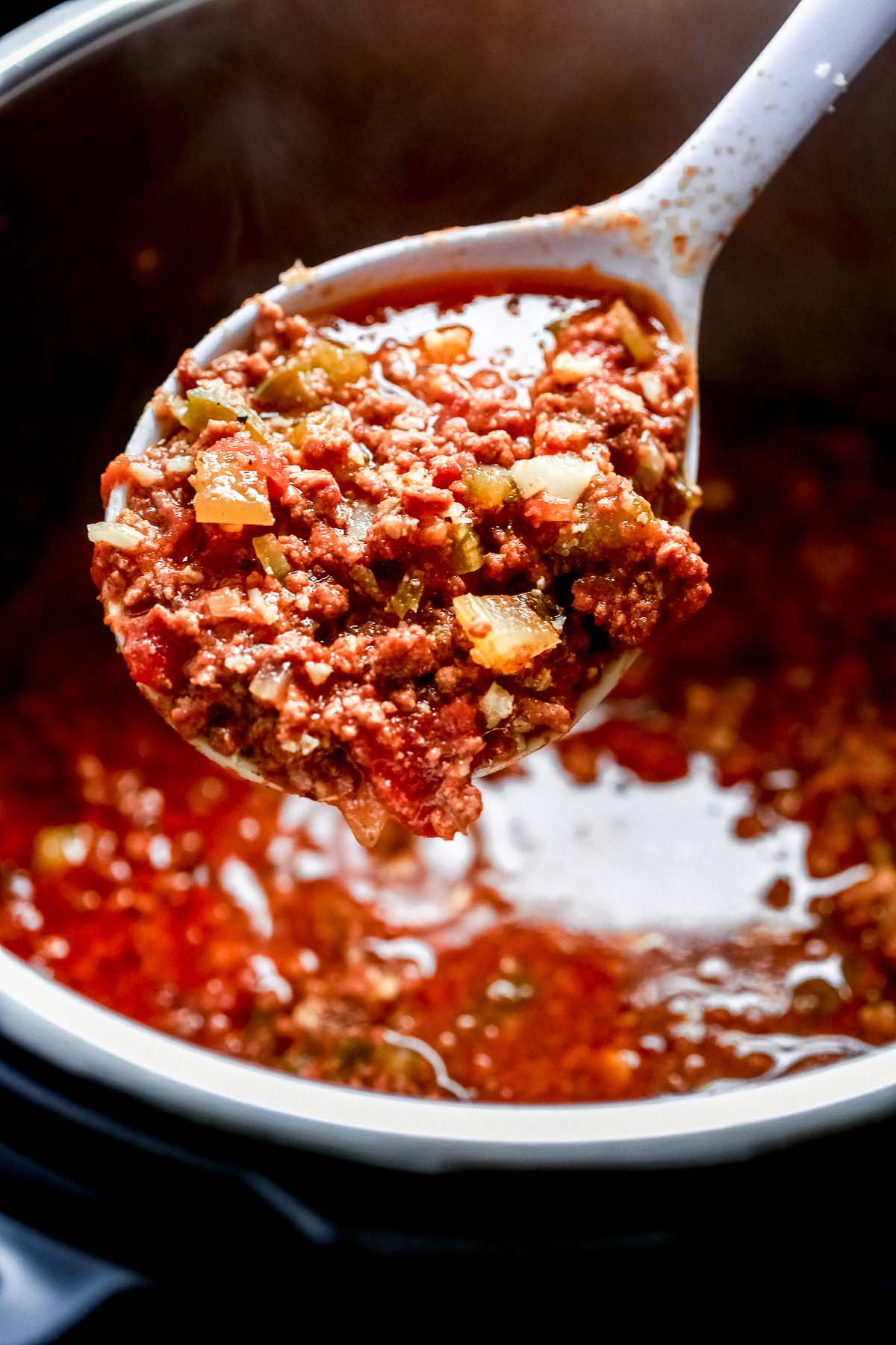 close up of chili on a spoon held over a pot