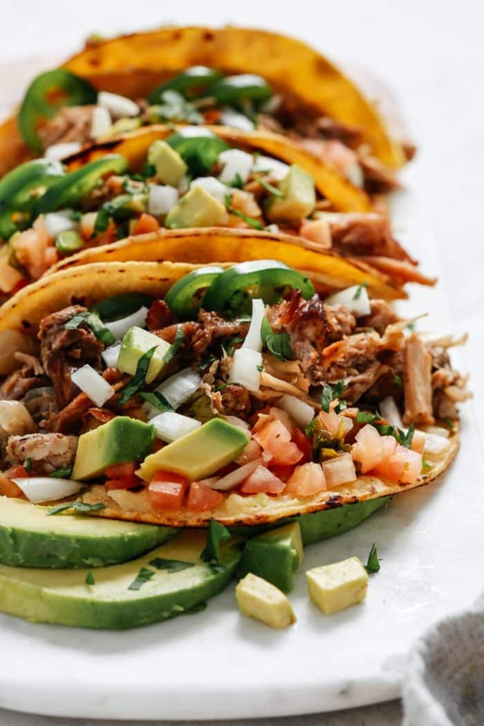 close up image of shredded Mexican pork with fresh avocado in taco shells