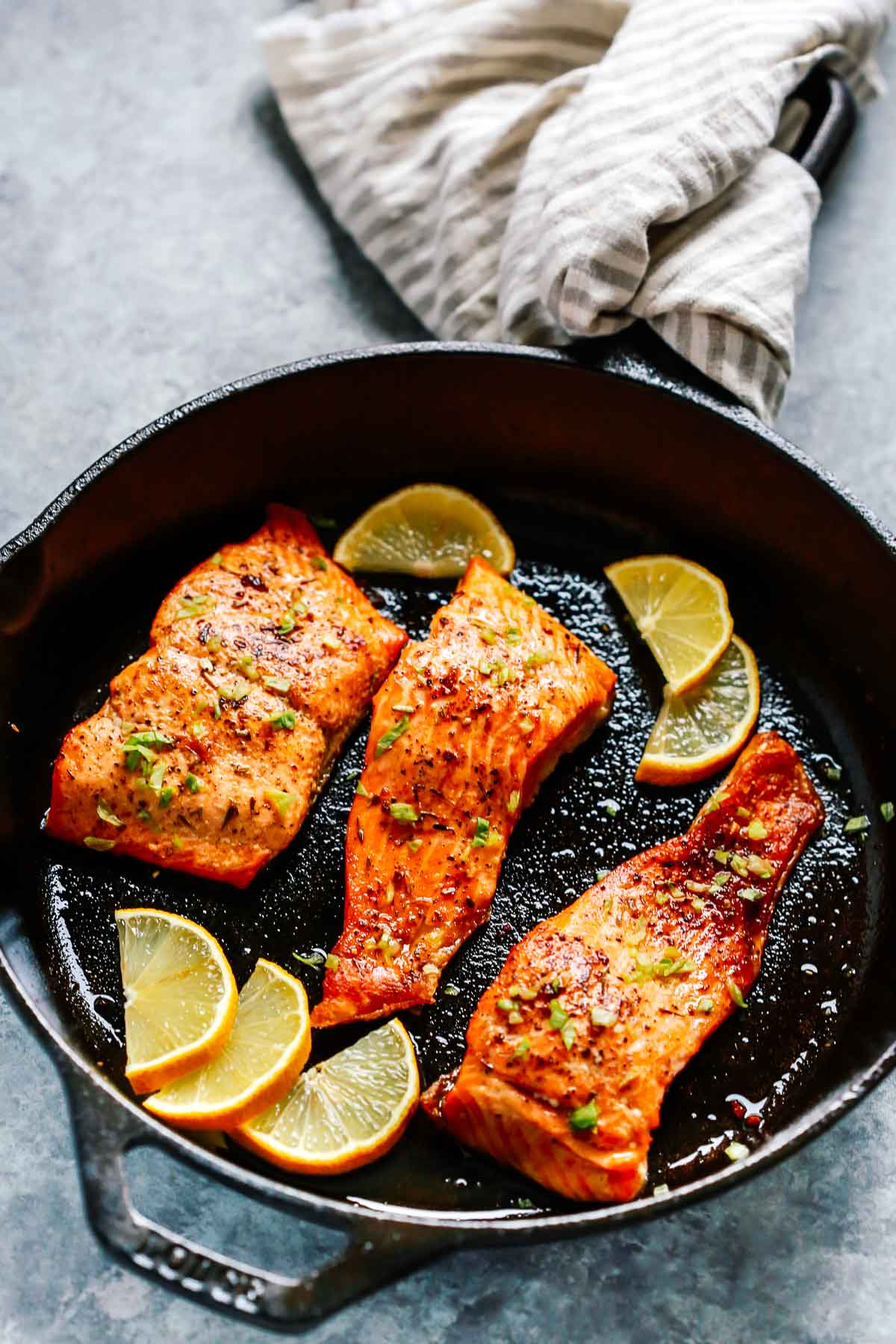 cast iron pan containing broiled salmon
