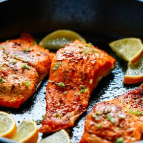 close up of broiled salmon in a cast iron skillet