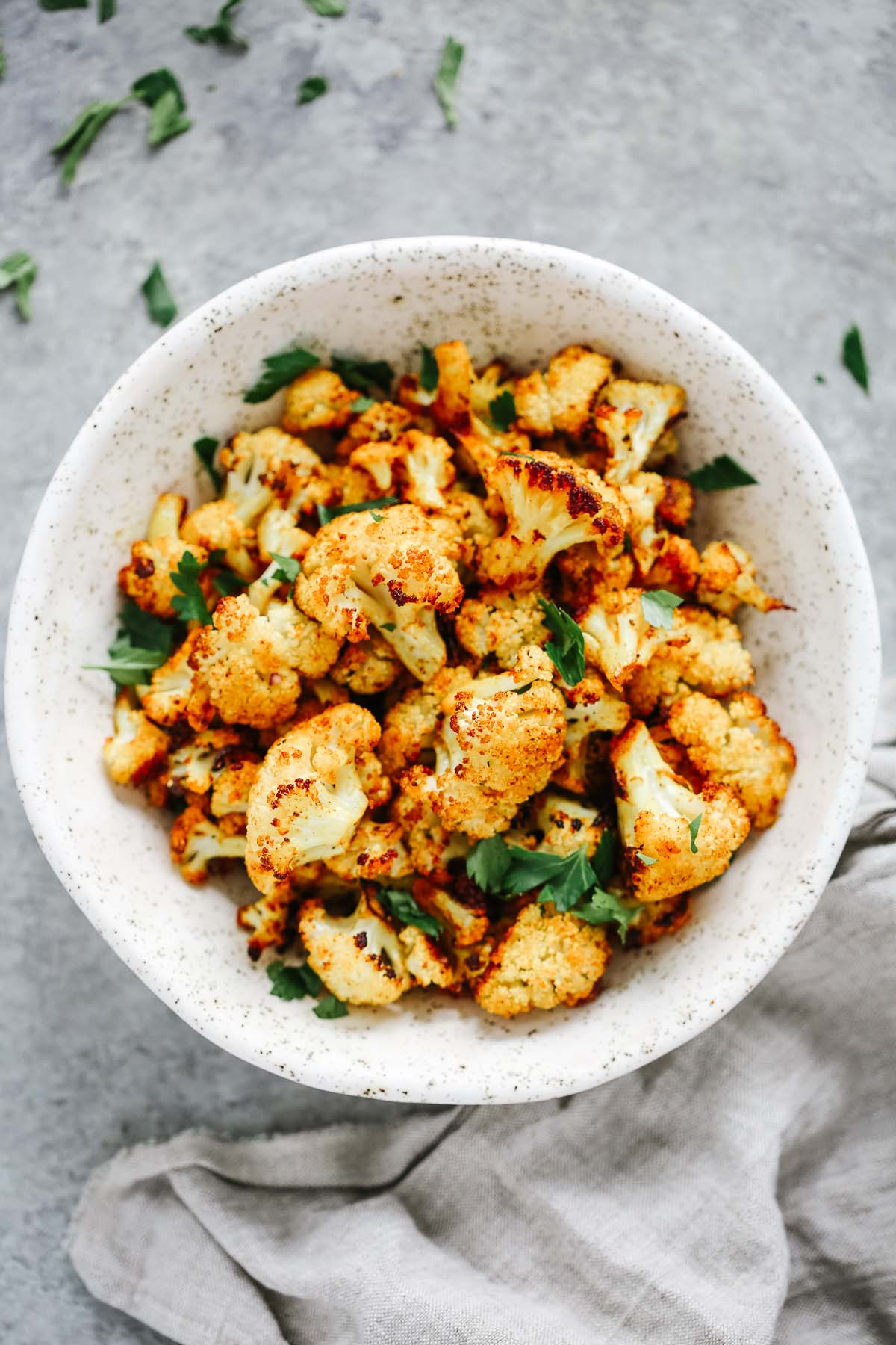 Overhead photo of roasted cauliflower in a white bowl.