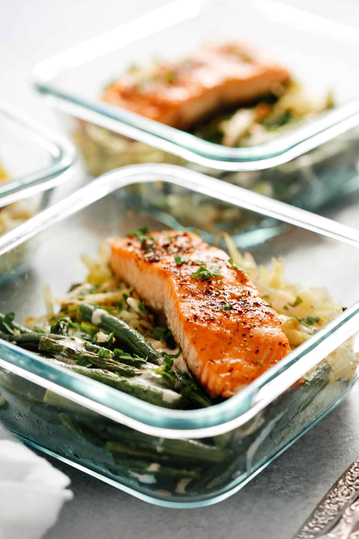 broiled salmon filet in square glass container with green beans and cabbage