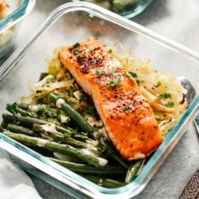 broiled salmon filet in meal prep container with green beans and cabbage