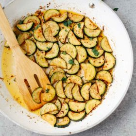 sautéed zucchini in a white bowl with wooden spoon