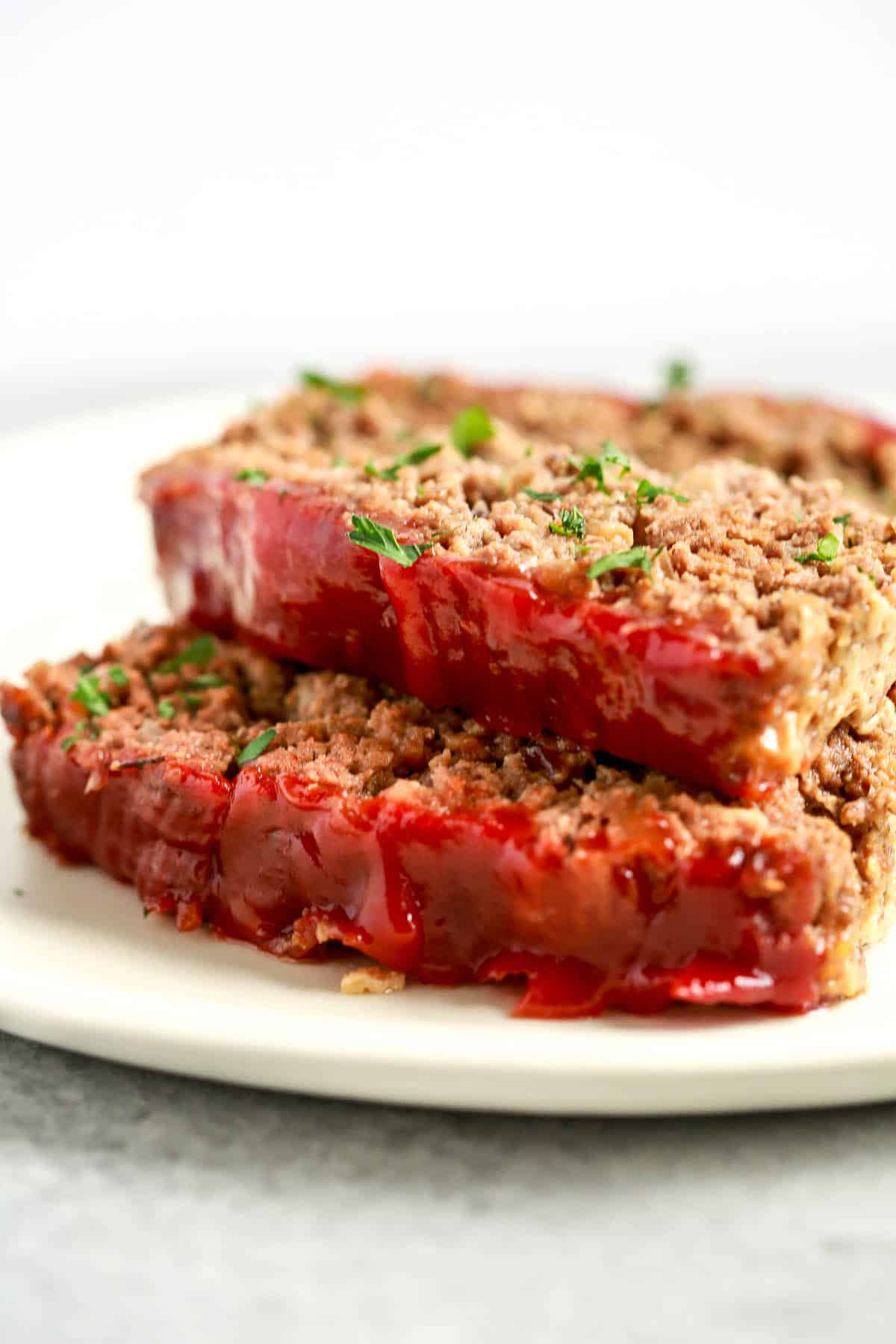 close up image: two slices of healthy meatloaf with tomato sauce on top
