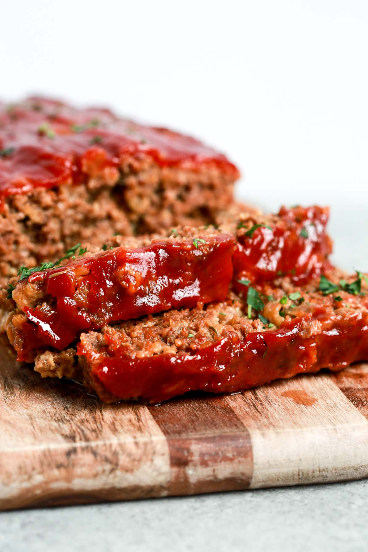 slices of homemade meatloaf with tomato sauce on top on cutting board