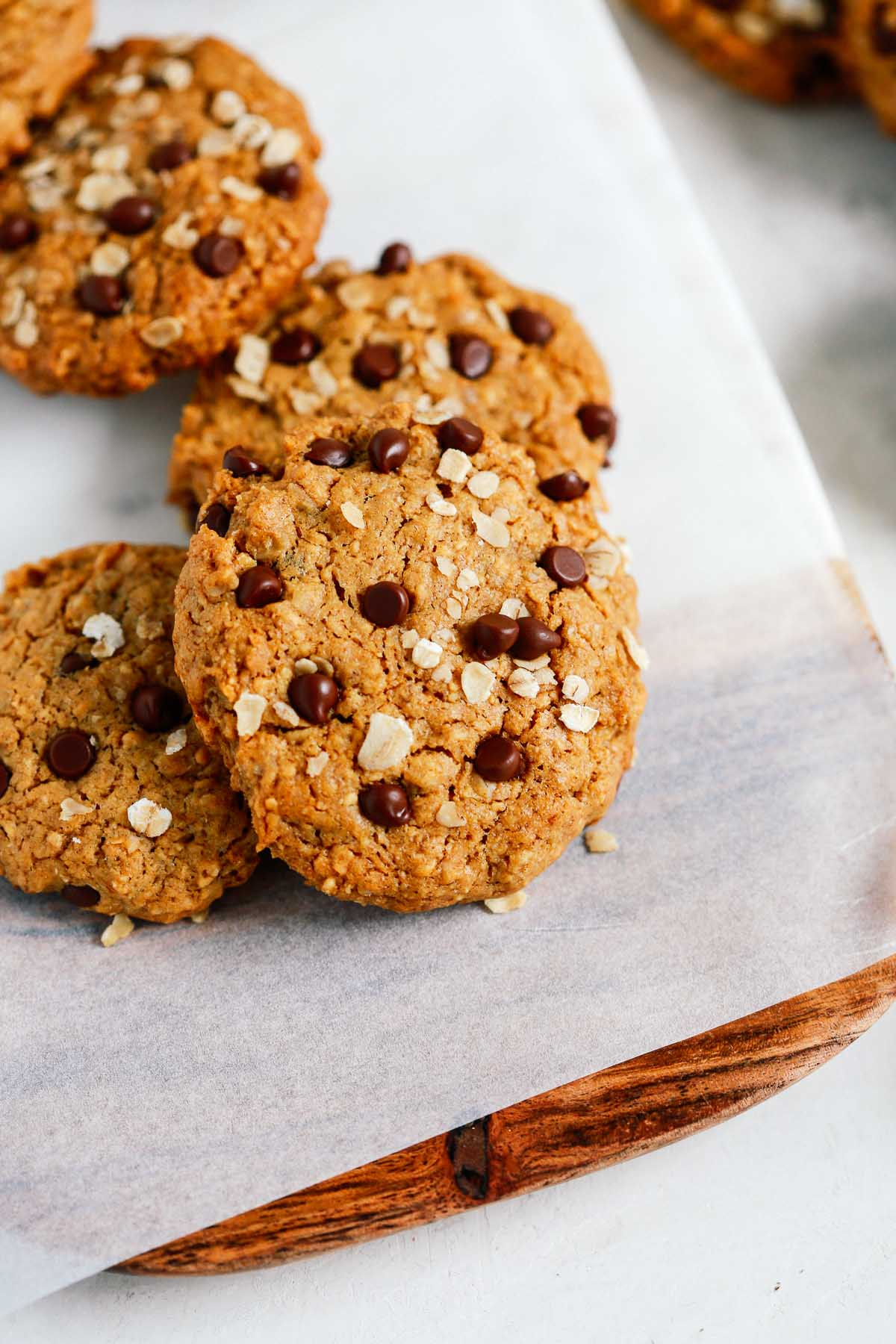 Peanut butter oatmeal cookies with chocolate chips on a cutting board