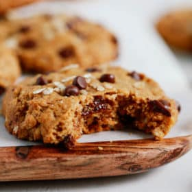 Chocolate chip cookies with a bite taken out of it on a wooden serving board