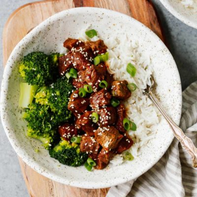Instant Pot Korean beef on white plate with sides of white rice and steamed broccoli