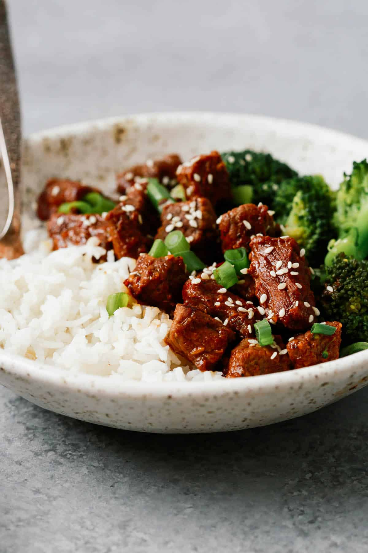 plate of Asian spiced beef, fluffy white rice, and side of steamed broccoli