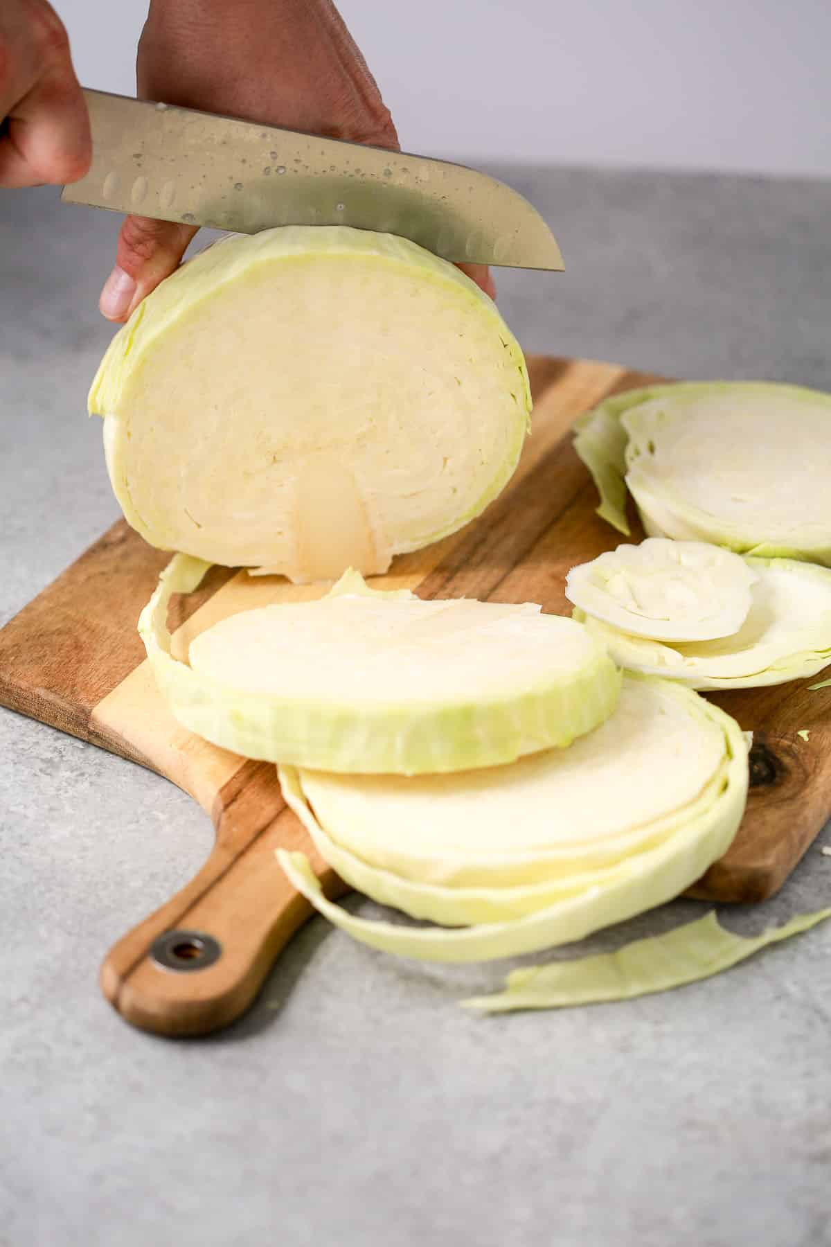 slicing cabbage steaks on a cutting board
