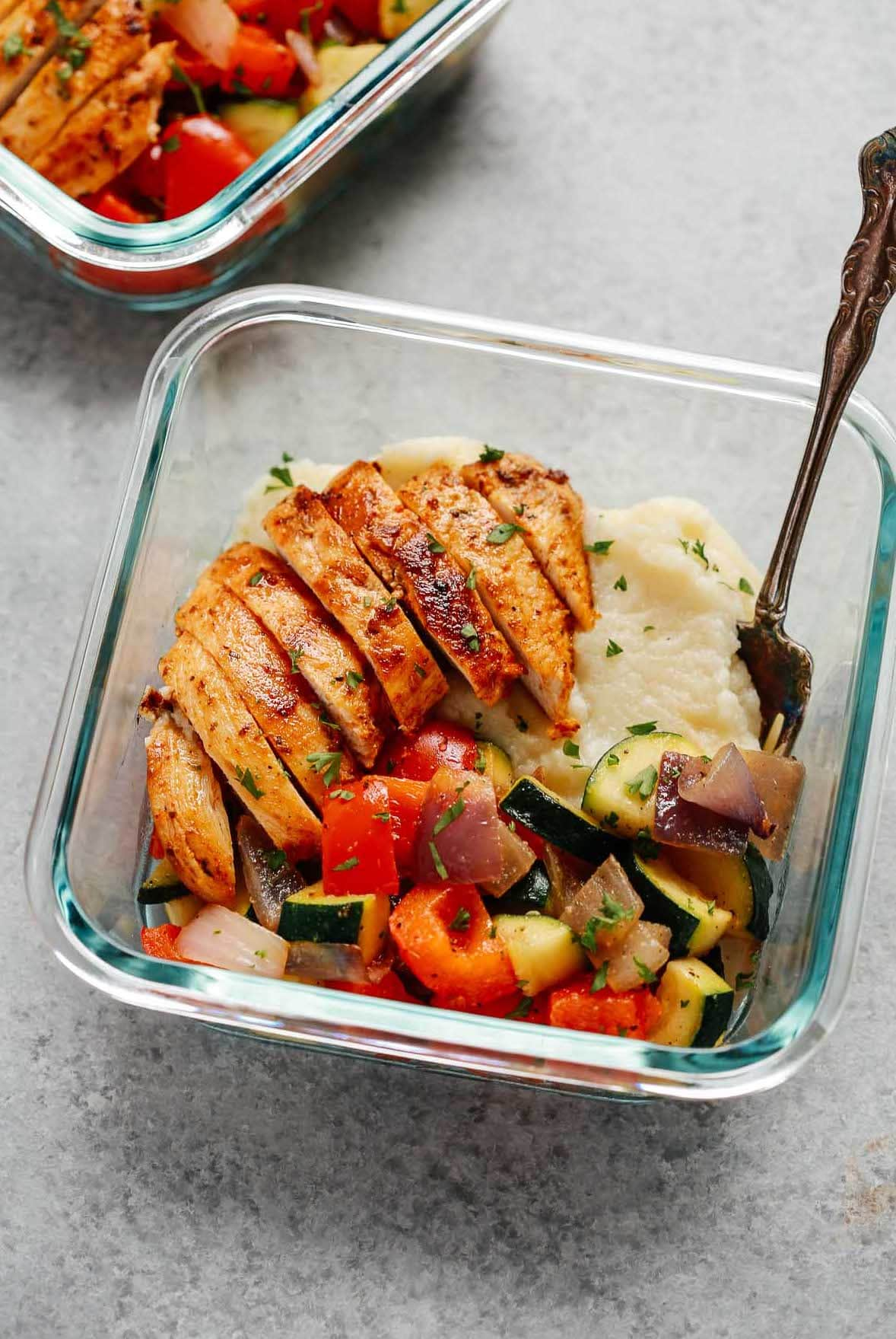 sliced baked chicken breast, cooked mixed vegetables and cauliflower mashed potatoes in square glass meal prep container