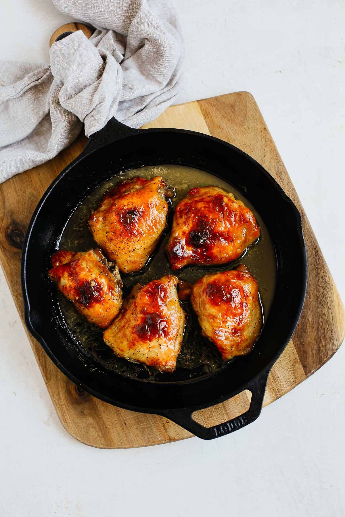 cast iron skillet with dijon chicken thighs on a wooden cutting board