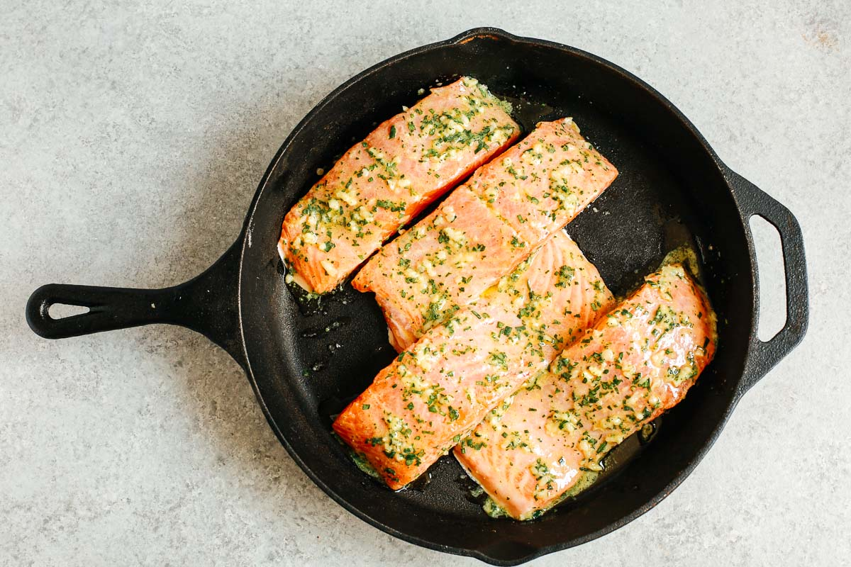 cast iron skillet with raw salmon fillets with mustard sauce