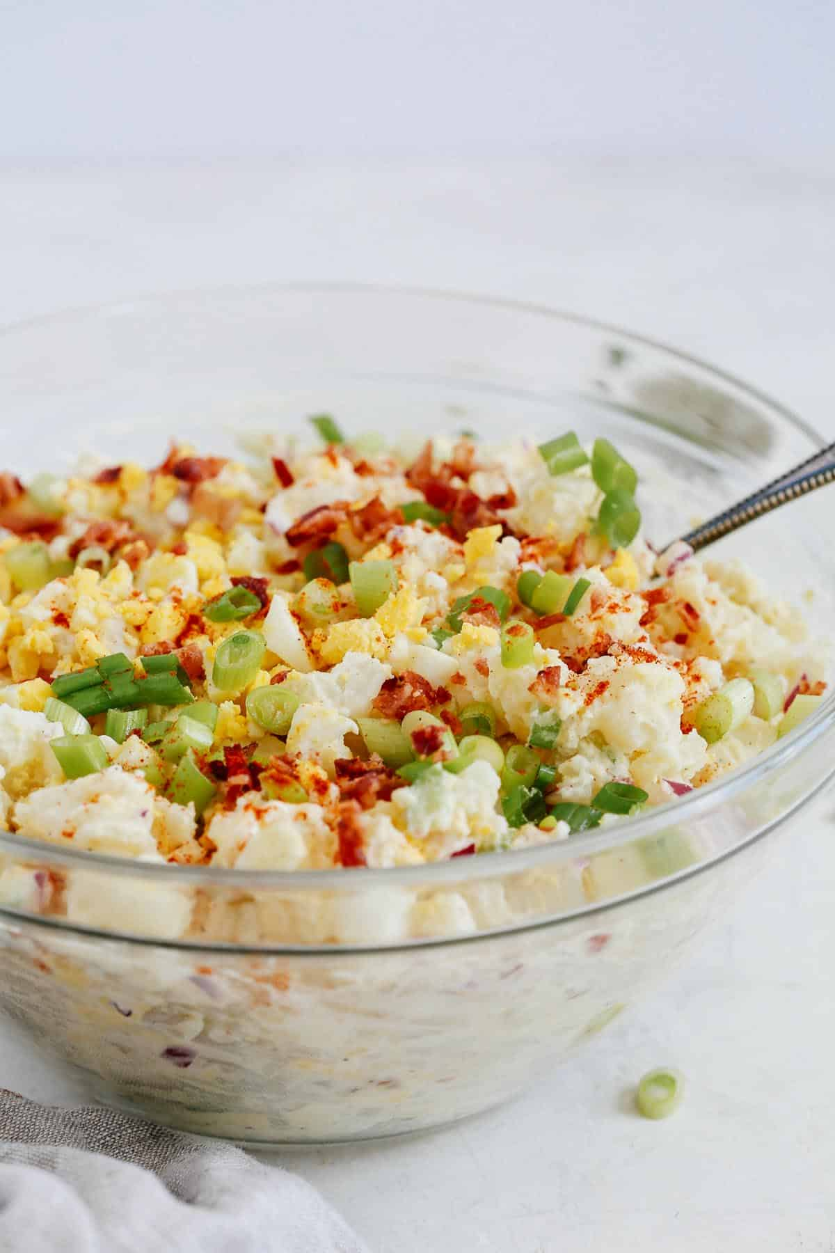 creamy potato salad in glass serving bowl