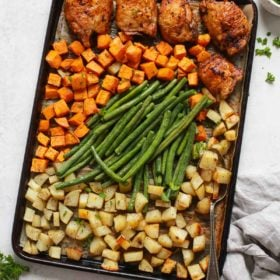 overhead view of a baking sheet containingchicken thighs and veggies