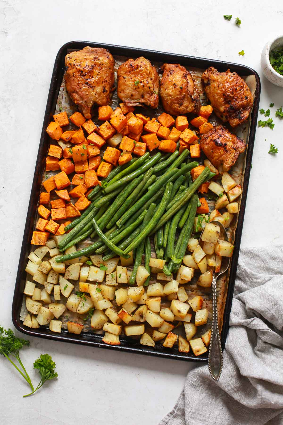 overhead view of a baking sheet containing vegetables and chicken thighs