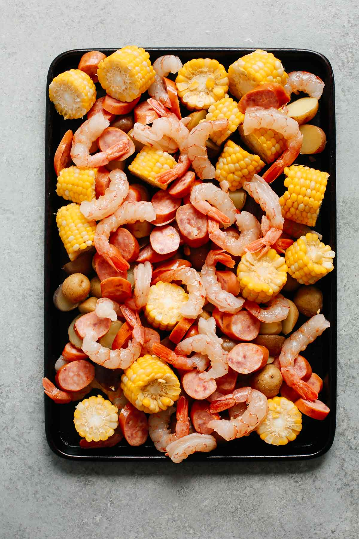 baking sheet with shrimp, sausage, corn, and pototoes