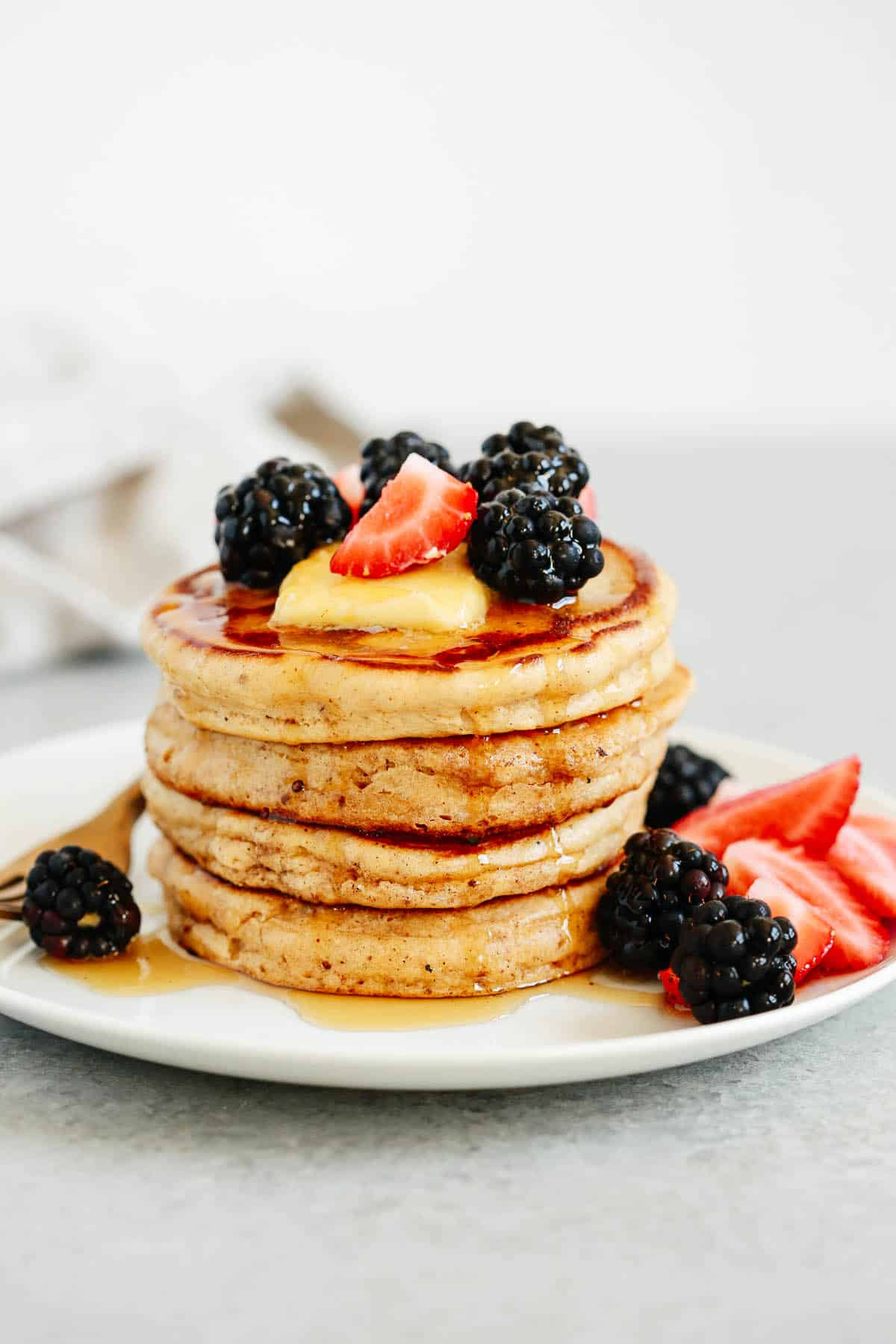 stack of gluten free pancakes topped with syrup and berries on a white plate