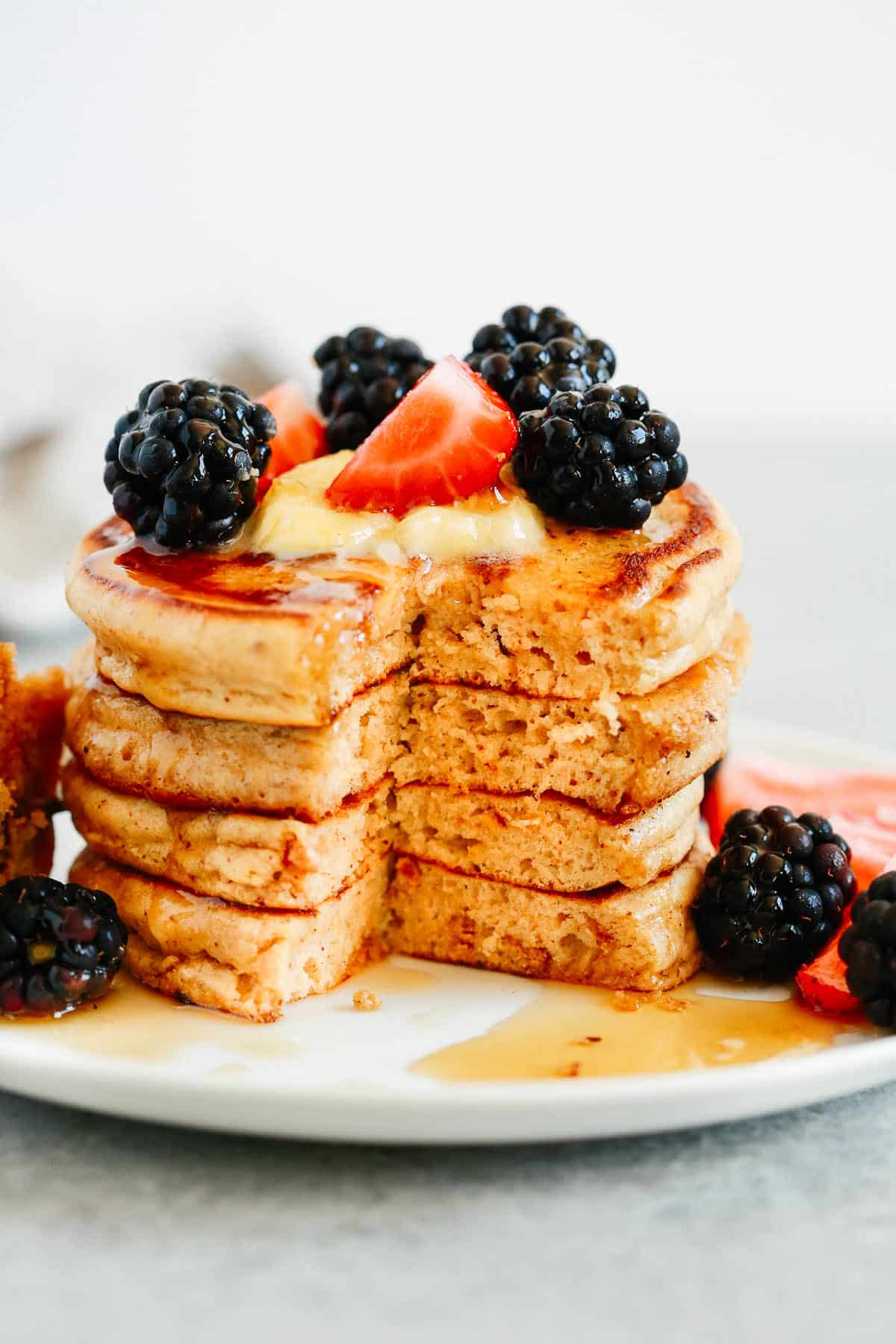 stack of peanut butter gluten free pancakes with berries that's been cut into