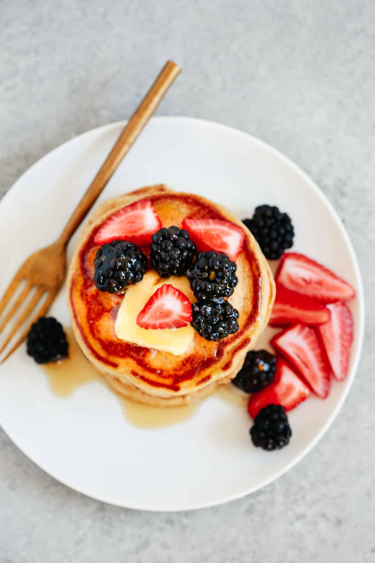 overhead photo of a stack of gluten free pancakes with berries on a white plate with a gold fork