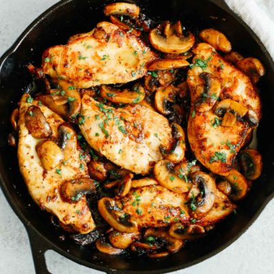 overhead photo of cooked chicken breasts and mushrooms in a cast iron skillet