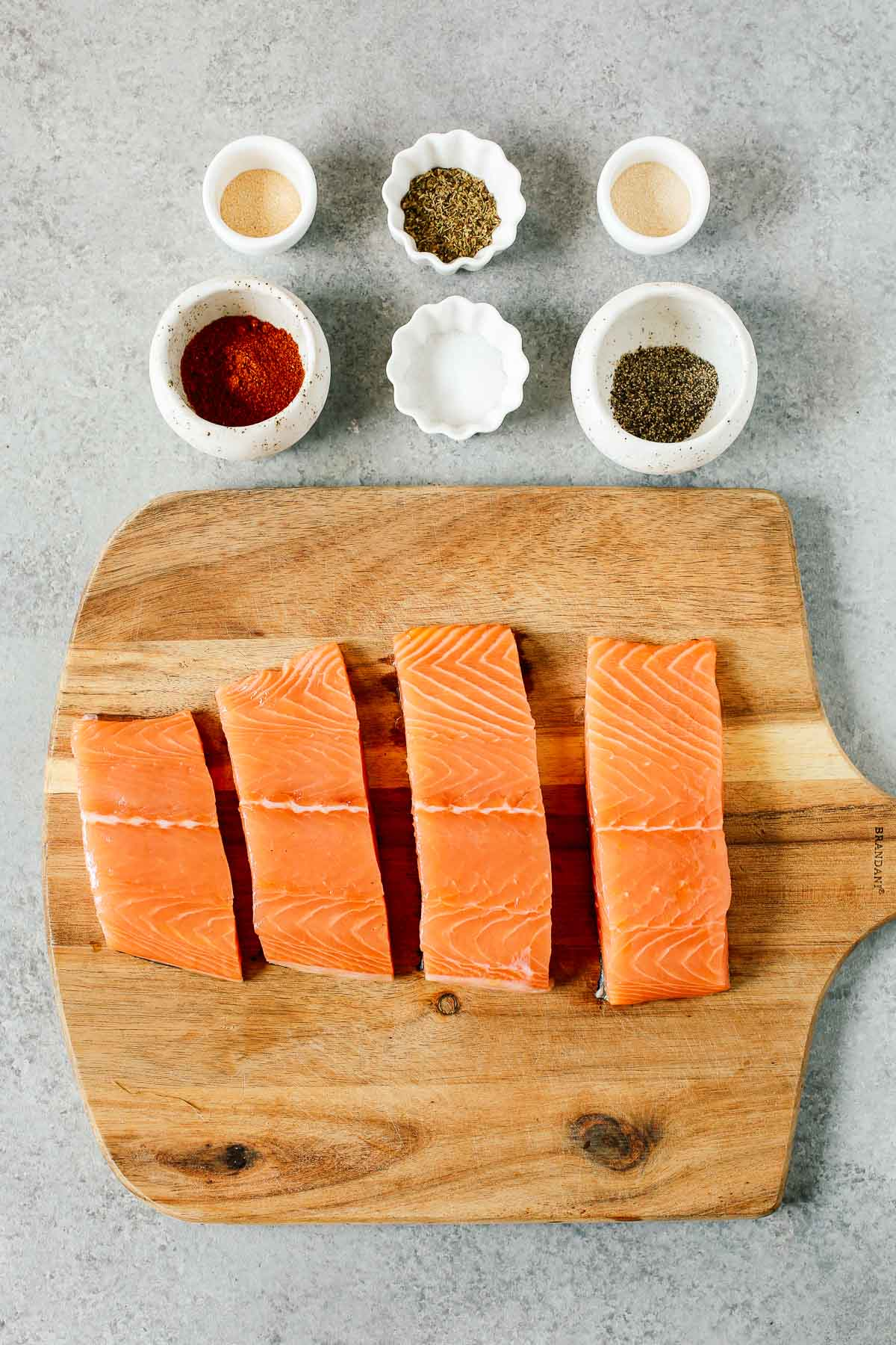 overhead image: 4 raw fish fillets and 6 small prep bowls with spices to make a blackened salmon recipe