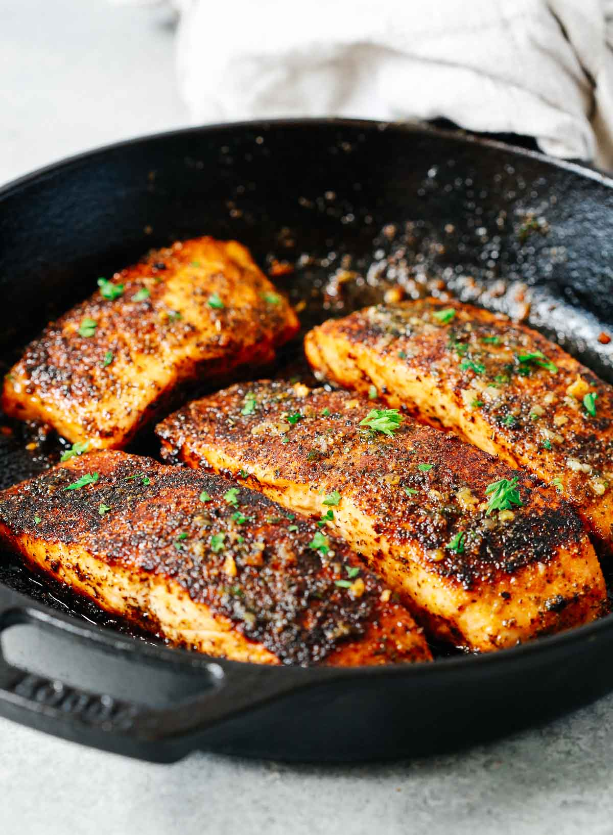 cooking four heavily seasoned fish fillets in a cast iron skillet