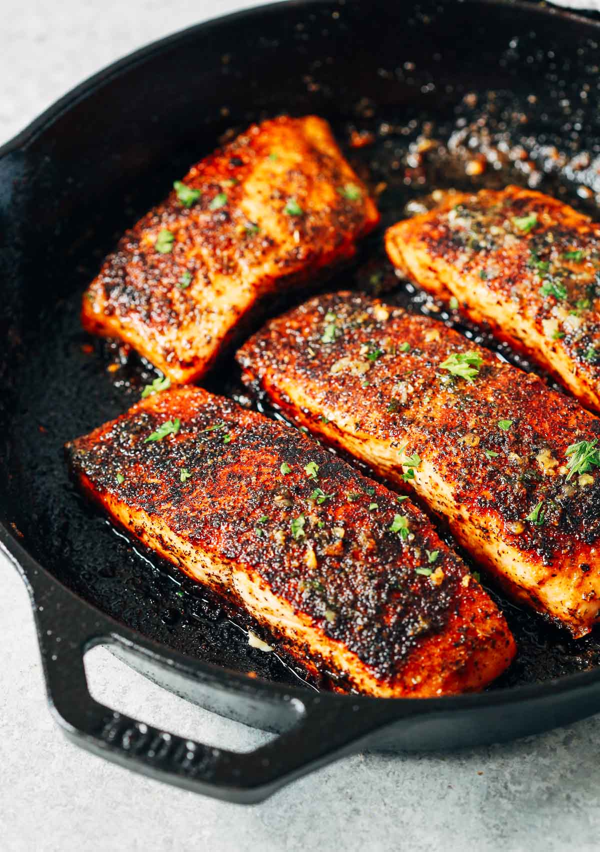 overhead view of a white skillet containing Blackened salmon