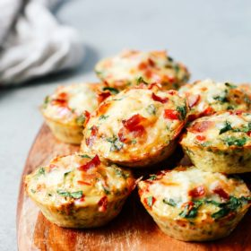 A close up of egg muffins on top of wooden serving board