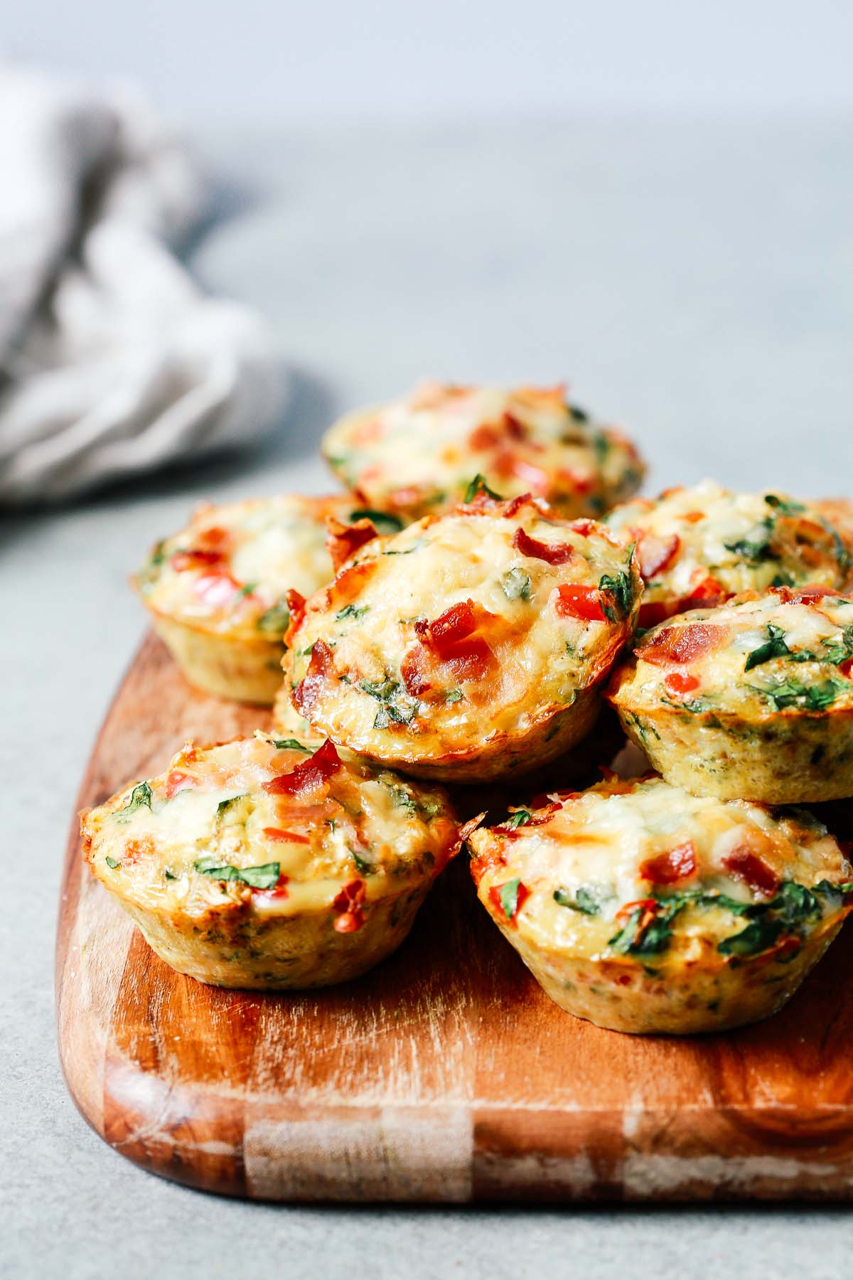 several breakfast egg muffins on a wooden serving board