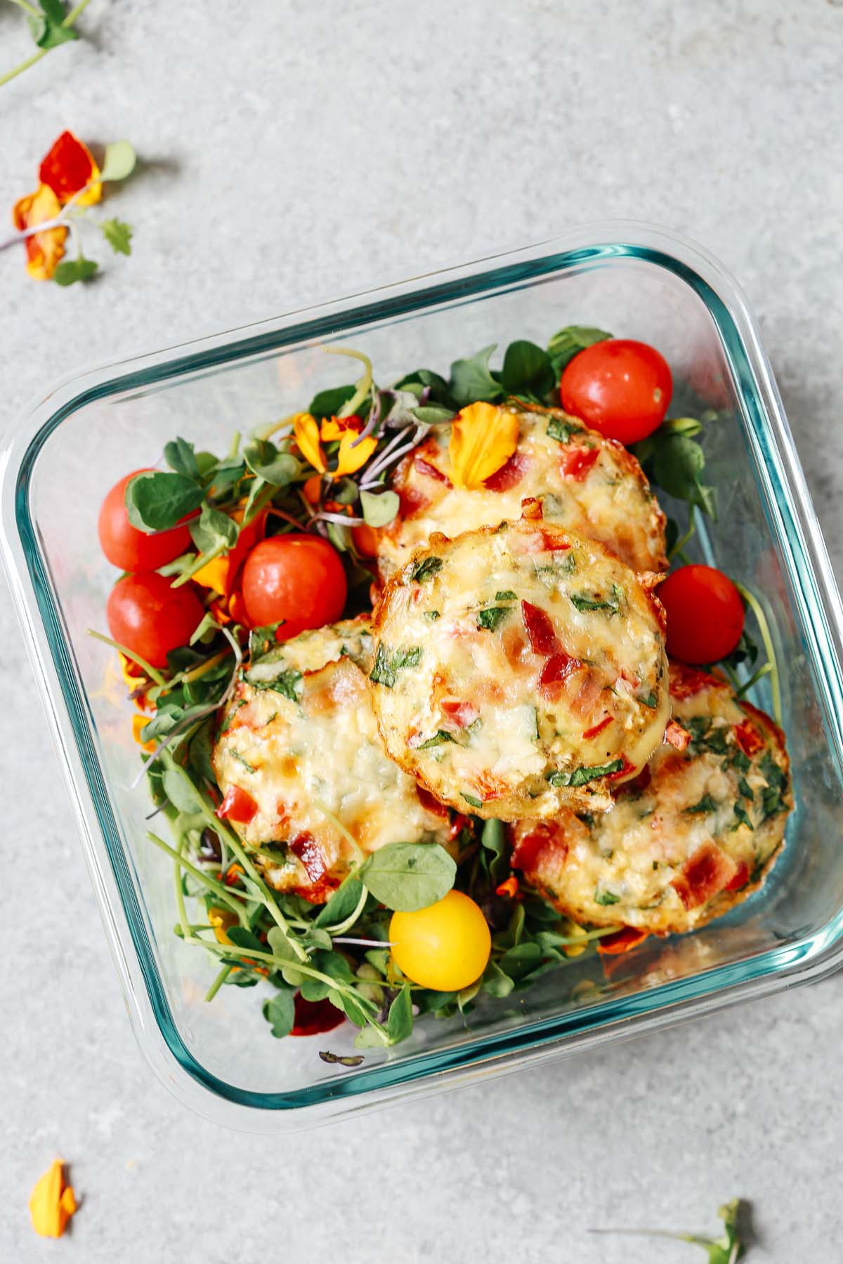 meal prep container with 3 breakfast egg muffins and cherry tomatoes on top of salad greens