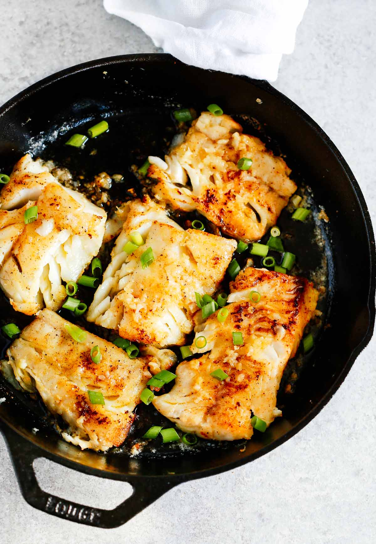 pieces of garlic butter cod cooking in cast iron skillet
