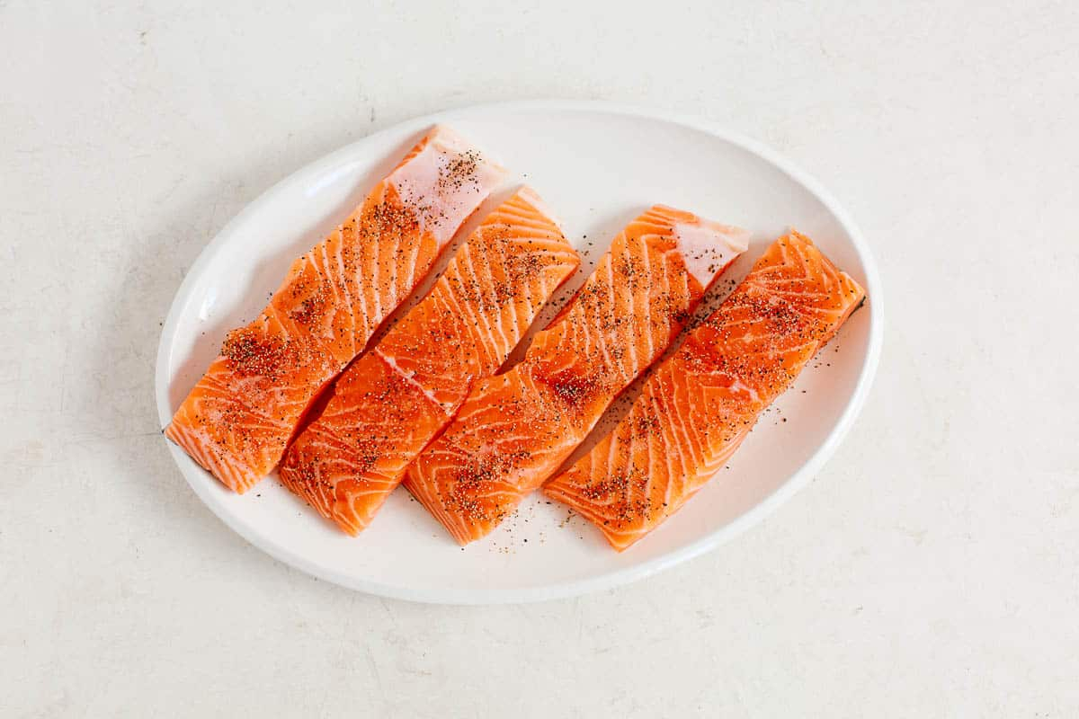 overhead image: four raw salmon fillets on a white platter for a pan seared salmon recipe