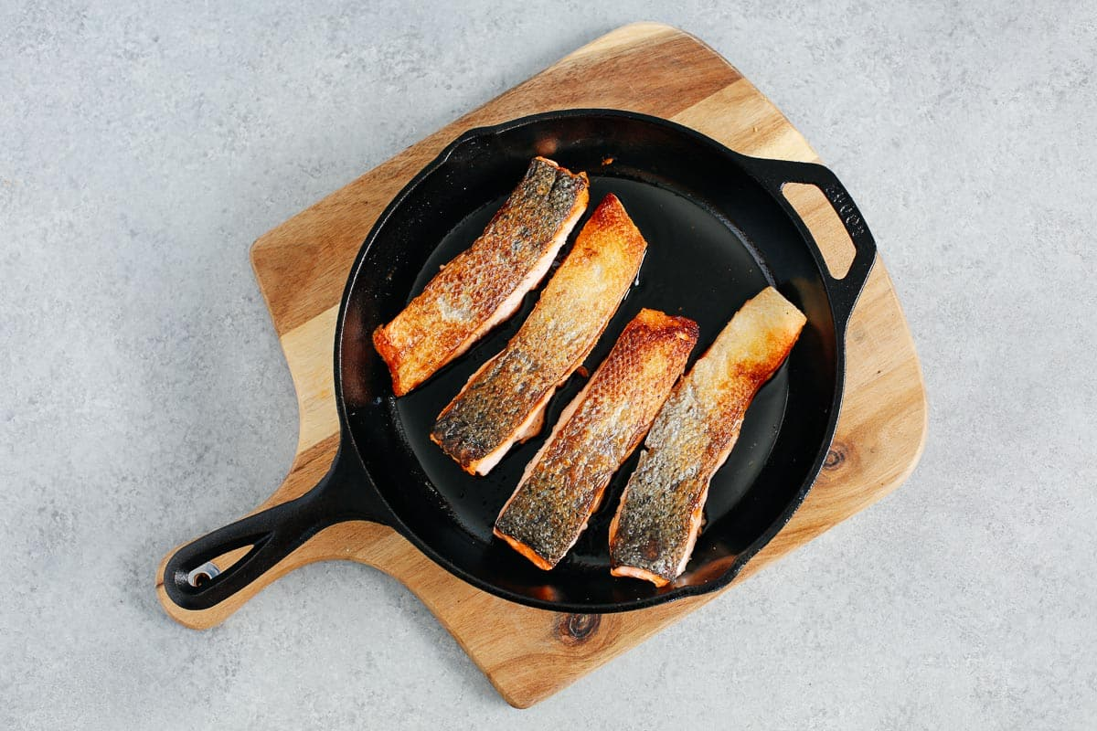 4 salmon fillets with crispy skin in a cast iron skillet