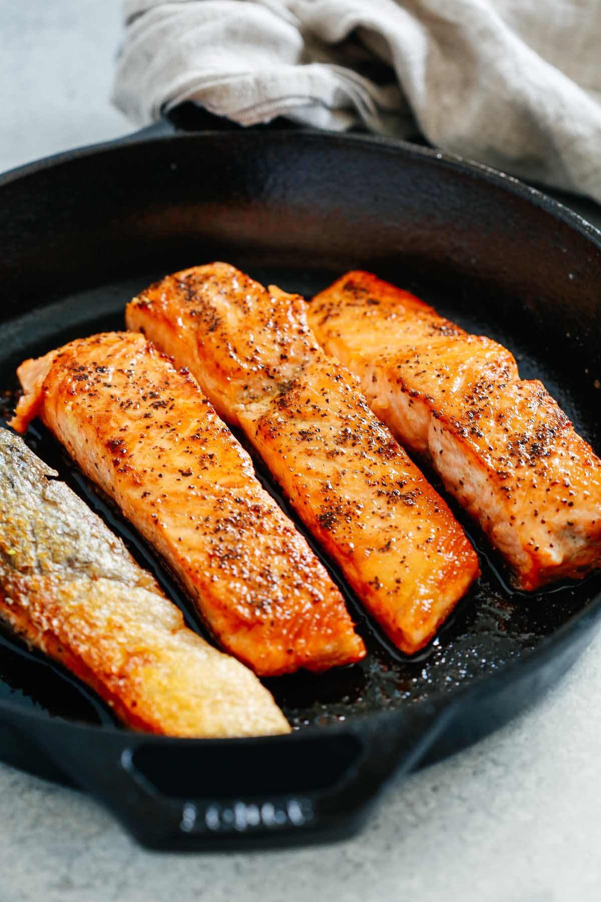 overhead view of a cast iron skillet containing pan seared salmon