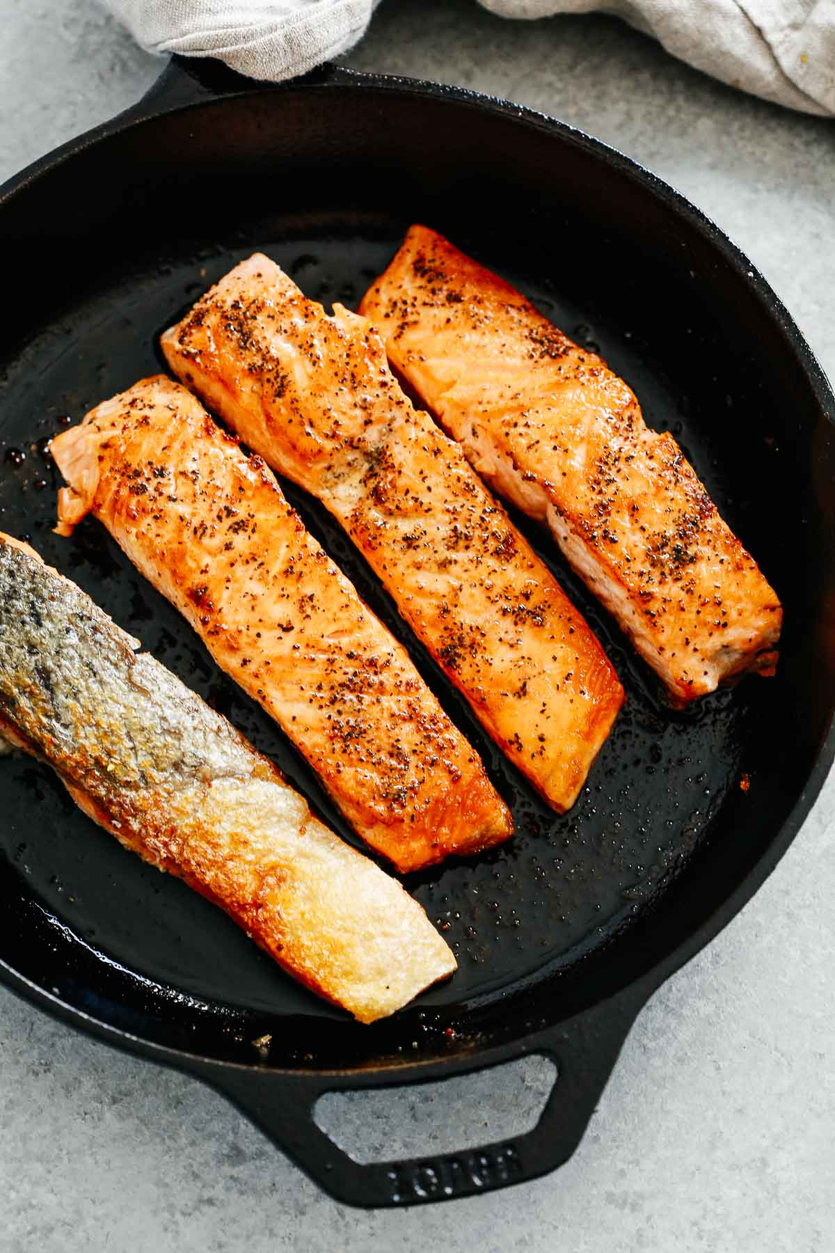 4 pieces of fish in black iron skillet