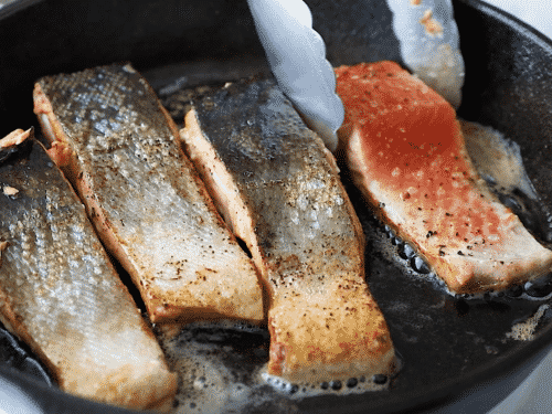 close up of filet salmon (skin side up) in a cast iron skillet