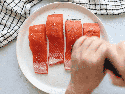 close up of raw filet salmon on a white plate