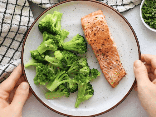 salmon on a white plate containing salmon and broccoli