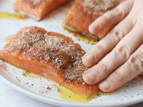 A close up of salmon fillets being with dried spices on top