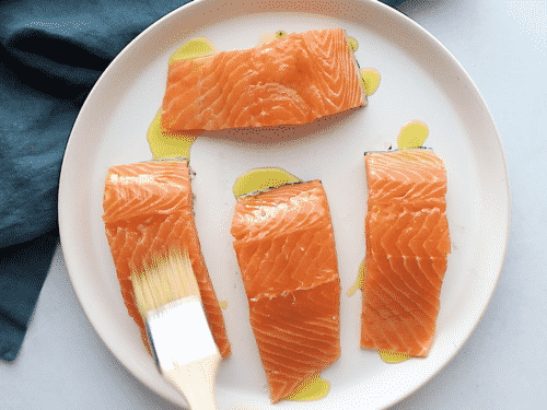 overhead view of a salmon being brushed with olive oil on a white plate